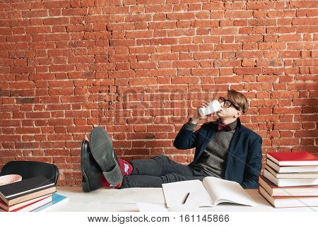 Tired man drinking coffee to continue study. Exhausted student need more energy to learn material, free space on brick wall background. Charging, education, motivation concept