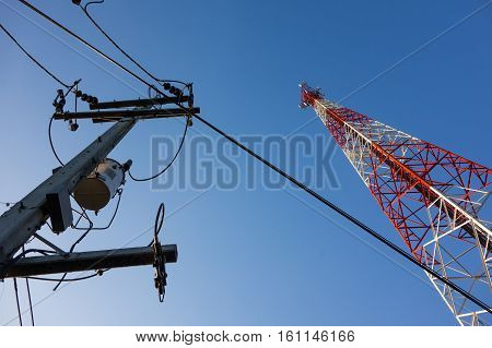 Red And White Mast With Communication Antennas On Blue Sky Background