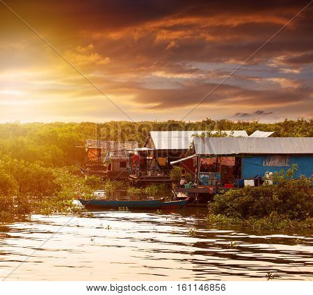 Beautiful sunset on Tonle Sap Lake and water village. Cambodia. The life of the local residents