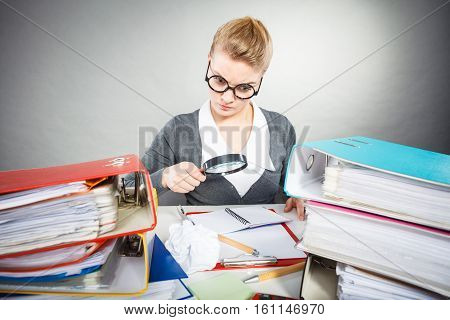 Exploration and work education. Focus secretary accountant businesswoman explore documents with big loupe. Woman surrounded by business equipment.