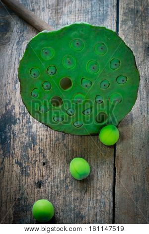 Three lotus seeds and calyx on wooden background