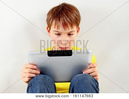 Sad Kid with Tablet Computer on the White Wall Background