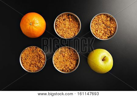 Set of four identical stainless steel cups with apple crumble dessert, one orange and one yellow apple shot from the top on black table