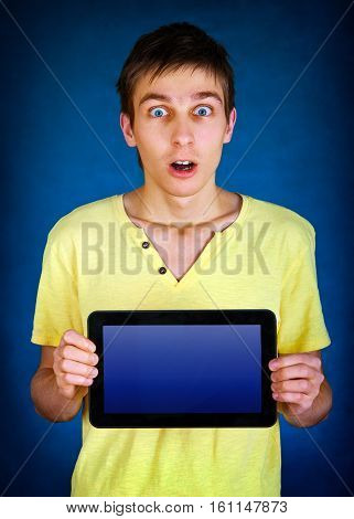 Surprised Young Man show a Tablet Computer on the Blue Background