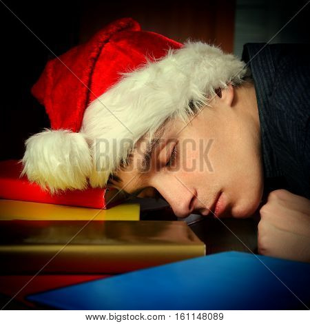 Toned Photo of Tired Student in Santa Hat sleep on the Books