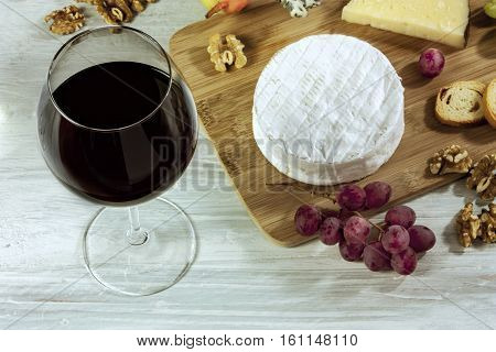 A photo of a tasting with a glass of wine, cheese, nuts, and grapes, on a wooden board