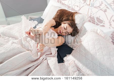 Beautiful girl awaking alone in bed, free space. Top view on young attractive woman stretching to wake up. Morning, bedroom, rest, awakening concept