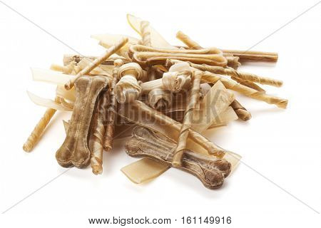 Variety of raw cowhide dog chewing bones and sticks isolated on white background