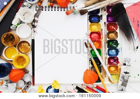 Blank sketchbook in drawing supplies frame flat lay. Top view on artist workplace with colorful dye and instruments, mockup. Art, workshop, painting, drawing, inspiration, craft, creativity concept