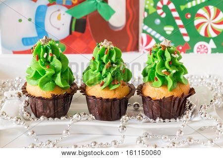 Christmas cupcakes on the background Christmas New Year gifts holiday decorated. Christmas trees shape capcakes for festive breakfast idea. Horizontal. Close.
