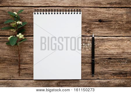 Empty white notebook with flowers and pen flat lay. Top view on blank sketchbook on grunge old wooden background, free space. Art, writing, idea, memory , planning concept