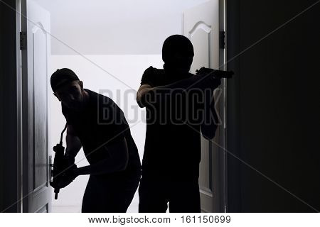 Thieves with gun entering the room