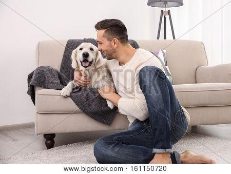 Cool dog and young man having fun at home