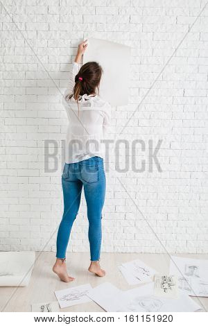 Back of woman hanging empty paper on wall mockup. Artist holding white whatman against white brick side of workshop, free space for text or advertisement