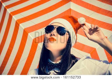 Portrait of a pretty girl in Santa Claus hat and sunglasses with bright painted lips next to a striped background. Toned effect