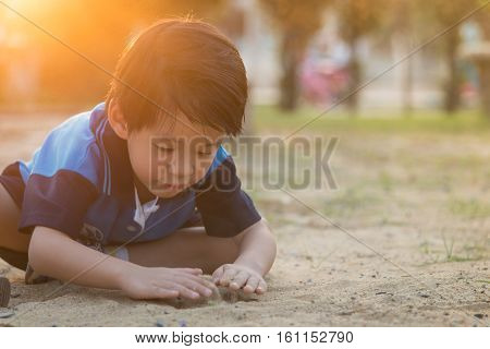 Asian child playing with sand in the playground