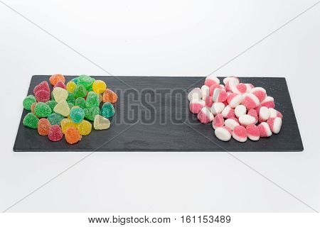 Colorful candy on a dark stone isolated on white background