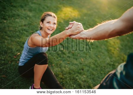 Man helping her girlfriend with focus on hands. Couple exercising in park.