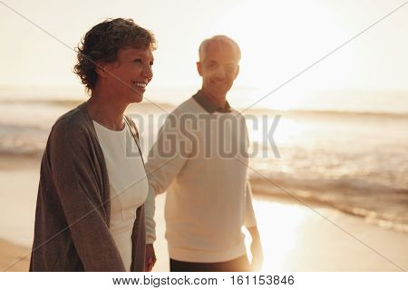Senior Couple Walking Along The Sea Shore