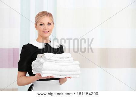 Chambermaid with pile of clean towels standing near window