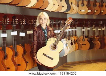 Female saleswoman holding guitar in shop