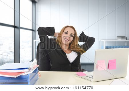 attractive 40s blond businesswoman working at office laptop computer sitting on the desk relaxed and smiling happy as if thinking of vacation at business district modern office in success concept