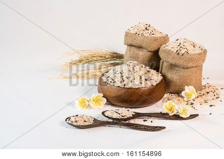 Jasmine rice and brown rice in a wooden bowl and paddy rice on white background