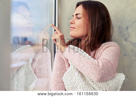 Close-up of charming girl in rosy sweater. Sitting by the window and embracing a lace pillow. Pretty girl with natural makeup, rosy lips resting at home