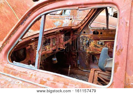 Old classic car stripped of parts taken in a countryside junkyard