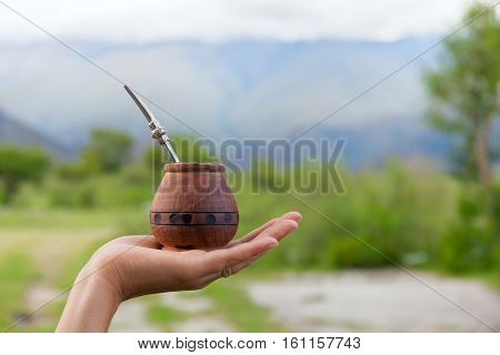 Yerba mate in a traditional calabash gourd, dry mate hand, space for your text