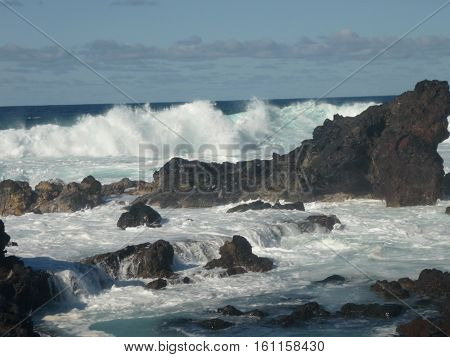 big white waves crashing into ocean rocks