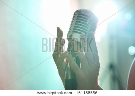 Female hands holding retro microphone, close up