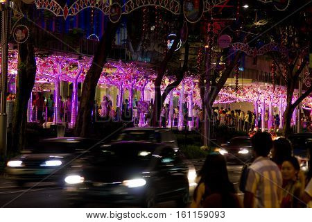 Singapore, Singapore - December 24, 2012: Night shot of a busy street in Singapore city. The street is decorated for Christmas and New Year celebrations.