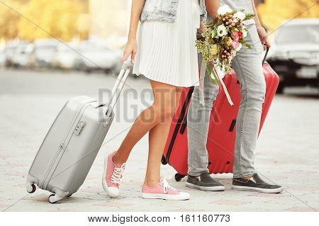 Just married couple with suitcases walking in the street