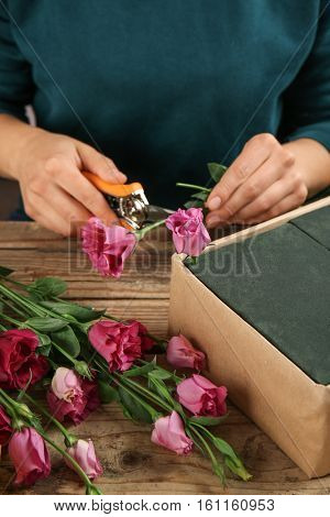 Female hands making beautiful flower composition on table
