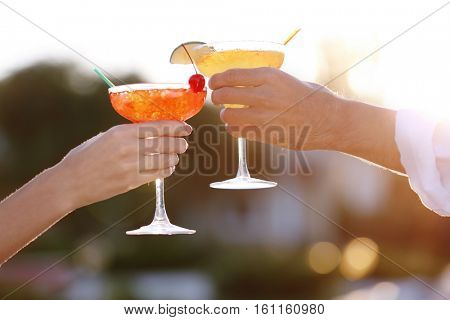 Male and female hands holding glasses with margarita cocktail on blurred background