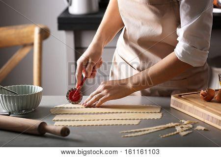 Woman cutting dough for ravioli on table