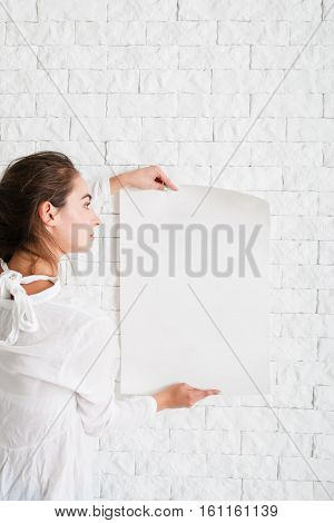 Young woman looking at empty sheet of paper, mockup. Female holding blank poster and reading information in it, copy space for text or advertisement
