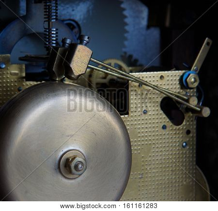 Mechanism of mantel clock with brass chimes and small bronze hammers local focusing on hammers