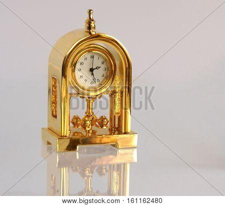 Retro gilded table clock on light gray background