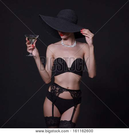 Sexy young woman in black lingerie and elegant hat.