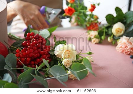 Beautiful flowers and berries on florists workplace