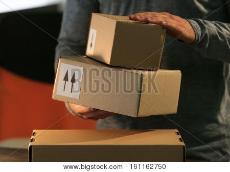 Deliverer holding carton boxes, closeup