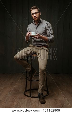 Full length portrait of a pensive bearded man sitting on chair and drrinking coffee isolated on a black wooden background