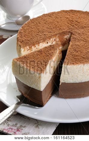 Cut a piece of chocolate with vanilla mousse cake covered cocoa
