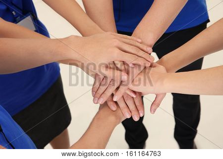 Team of friendly young people holding hands together