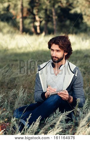 Author writing poem at nature, free space. attractive man sitting with notebook, came for inspiration to meadow. Relax, idea, thinking concept