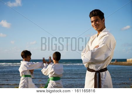 Teacher training children in karate and traditional martial arts. Simulation of fight near the sea. Portrait of instructor with boys in background