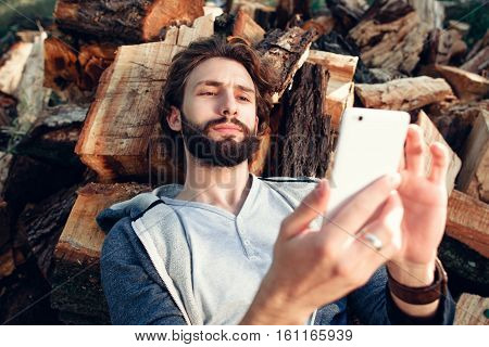 Portrait of man with smartphone on pile of wood. Bearded guy taking selfie or typing message on mobile phone, having rest on firewood. Communications, networking concept