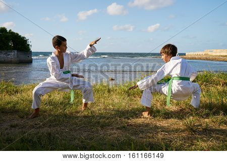 Children doing combat and extreme sports. Latino boys exercising in karate and traditional martial arts. Simulation of fight on the beach